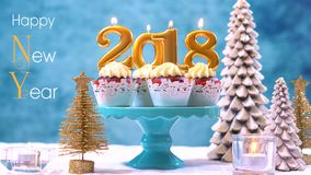 Happy New Year 2018 cupcakes. On a modern stylish, festive, blue gold and white Winter theme table setting, close up with Happy New Year text Royalty Free Stock Images