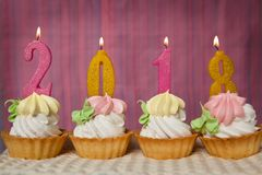Happy new 2018 year, cupcakes with number candles. On pink background Royalty Free Stock Image