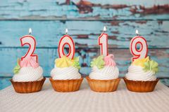 Happy new 2019 year, cupcakes with number candles on blue background. Happy new 2019 year, cupcakes with number candles on vintage blue wooden background stock photo