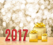 Happy new year 2017 3d rendering red glitter word and golden p. Resent on wood table with gold sparkling blurred bokeh light,Holiday greeting card