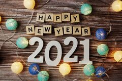 Happy New Year 2021 decorate with LED cotton ball on wooden background