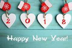 Happy New Year 2018.Decorative white wooden Christmas hearts and red mittens on blue wooden background with copy space. Selective focus Royalty Free Stock Photo