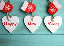Happy New Year.Decorative white wooden Christmas hearts and red mittens on blue wooden background.Winter holidays concept.  Royalty Free Stock Images