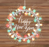 Happy new year design on wooden texture. Wreath of bright light garlands Stock Images