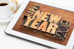 Happy New Year 2015 on digital tablet. 2015 Happy New Year greetings - text in vintage letterpress wood type blocks on a digital tablet with a cup of coffee royalty free stock photography