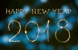 Happy new year and digits 2018. Written with sparklers and bokeh isolated on black Royalty Free Stock Image