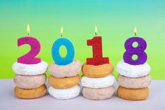 Happy New Year 2018 with donuts. Donuts stacked with candles celebrating Happy New Year, 2018 burning bright. Blue green yellow textured background. Cake Stock Photo
