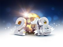Happy New Year 2018 environmental greetings for change. Greetings and silver New Year date 2018, composed with a gold planet earth, on a blurry blue background Royalty Free Stock Photography
