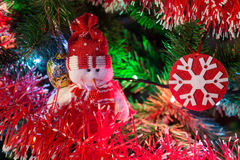 Happy new year with evergreen tree, snowman and snowflake toys and colorful illumination in red palette Royalty Free Stock Photography