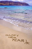 Happy new year and exclamation point written in the sand Stock Photo