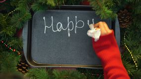 Happy New Year, female hand writing word with cream on baking tray, december. Stock footage stock footage