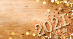 Happy New Year festive background with golden numbers 2021 and Christmas decorations on vintage wooden table top view