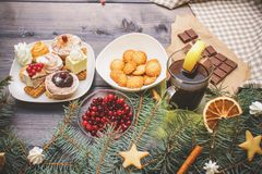 Happy New Year fir branches decorated with gingerbread stars, cinnamon sticks, dried orange slices and meringue peaks, bright stock photos