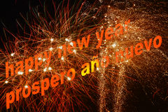 Happy new year in fireworks. Happy new year written in English and Spanish with a spectacular firework in the background Royalty Free Stock Image