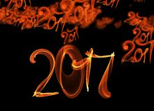 Happy new year 2017 flying digits numbers written with fire flame light on black background.  Royalty Free Stock Images