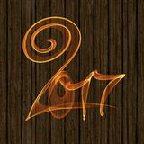 Happy new year 2017 flying digits numbers written with fire flame light on wooden background.  Stock Photography