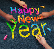 Happy New Year Friends. Concept with a group of hands representing ethnic groups of young people holding chalk cooperating together as a diverse group Royalty Free Stock Photo