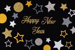 Happy New Year glittery text with star confetti against black royalty free stock images