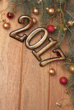 Happy new year 2017 gold figures  on the wooden background with Christmas decorations close, balls and gifts Stock Photography