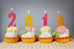 Happy new year 2018, golden and pink number candles on cupcakes. With gray background Stock Image