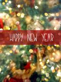 Happy New Year greeting card on blurred background with decorated natural green fir tree with red golden silver glittering balls stock image