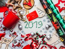 Happy New Year greeting card. Colorful Christmas decorations. And toys, warm socks with Santa Claus, a red mug and ribbons on a white, wooden surface. Top view royalty free stock photography