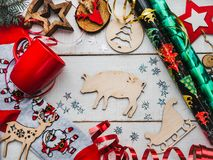 Happy New Year greeting card. Colorful Christmas decorations. And toys, warm socks with Santa Claus, a red mug and ribbons on a white, wooden surface. Top view stock images