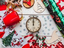 Happy New Year greeting card. Colorful Christmas decorations. And toys, warm socks with Santa Claus, a red mug and ribbons on a white, wooden surface. Top view stock photos