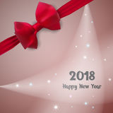 2018 Happy New Year. Greeting card. The illumination on the background. Decorated with a red bow. Stock Images