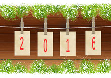Happy New Year 2016. Greeting New year card in 2016. Happy New Year 2016 numbers on cards hanging on a rope and clothespins. Wooden fence premise with fir Royalty Free Stock Photos