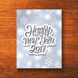 Happy New Year 2017 greeting card vector design. Happy New Year 2017 hand lettering text on paper label over glowing winter background. Vector greeting card stock illustration