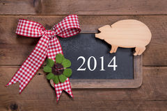 Happy new year 2014 - greeting card on a wooden background. With a lucky pig and a green clover with a red checked ribbon Royalty Free Stock Photos