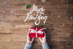 Happy New Year greeting text and gift on wood background stock photography