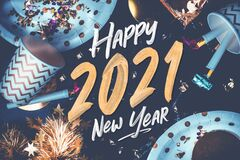2021 happy new year hand brush storke font on marble table with party cup,party blower,tinsel,confetti.Fun Celebrate holiday party