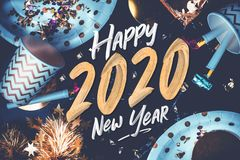 2020 happy new year hand brush storke font on marble table with party cup,party blower,tinsel,confetti.Fun Celebrate holiday party