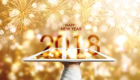 Happy New Year 2018, Hand holding digital tablet with luxury gold Bokeh fireworks background Stock Images