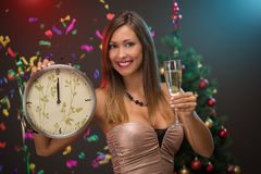 Happy New Year. Happiness beautiful woman celebrating New Year. She is showing midnight on the clock and toasting with champagne. Confetti is the air Stock Images