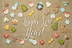 Happy New Year! Holiday greeting written among decorative gingerbread cookies. Stock Photography
