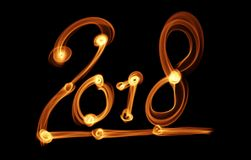 Happy new year 2018 isolated numbers lettering written with fire flame or smoke on black background.  Stock Photos