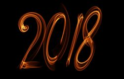 Happy new year 2018 isolated numbers lettering written with fire flame or smoke on black background.  Royalty Free Stock Images