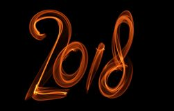Happy new year 2018 isolated numbers lettering written with fire flame or smoke on black background.  Stock Photography