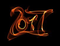Happy new year 2017 isolated numbers lettering written with fire flame or smoke on black background.  Royalty Free Stock Photos