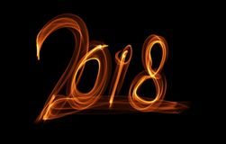 Happy new year 2018 isolated numbers lettering written with fire flame or smoke on black background.  Royalty Free Stock Photo