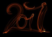 Happy new year 2017 isolated numbers lettering written with fire flame or smoke on black background.  Royalty Free Stock Images
