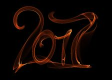 Happy new year 2017 isolated numbers lettering written with fire flame or smoke on black background.  Stock Photos