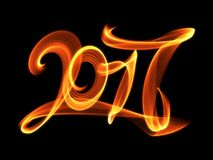 Happy new year 2017 isolated numbers lettering written with fire flame or smoke on black background.  Stock Photography
