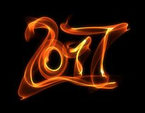 Happy new year 2017 isolated numbers lettering written with fire flame or smoke on black background.  Royalty Free Stock Photo