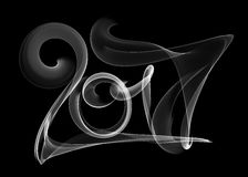 Happy new year 2017 isolated numbers lettering written with white fire flame or smoke on black background.  Stock Images