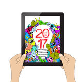 Happy new year 2017. Isolation man hand holding the tablet and Monster idea.  Royalty Free Stock Image