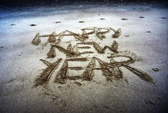 Happy New Year lettering on the beach. Happy new year written on sand at sunset. Happy New Year lettering on the beach. `Happy New Year` drawn on sand on a Stock Images